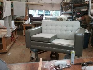 Loveseat with a mix of leather and fabric.